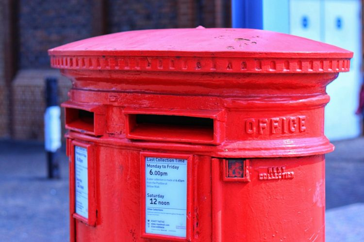 Red British letterbox with two slots